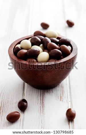 Small chocolate easter eggs in brown bowl - stock photo
