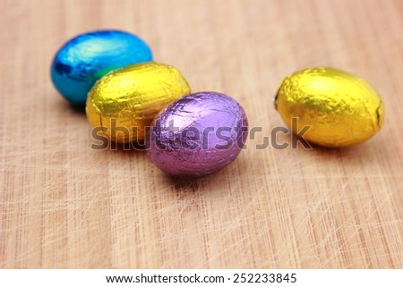 small chocolate eggs over wooden background