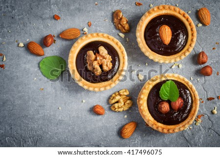 Small Chocolate Tarts decorated with different nuts on a gray stone background, space for text - stock photo