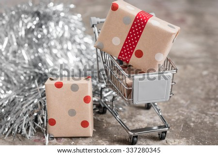 small christmas gifts in a shopping cart, with tinsel - stock photo