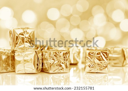 Small Christmas gifts in shiny golden paper, bokeh lights background - stock photo