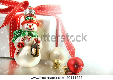 Small christmas ornament with gift against white background - stock photo