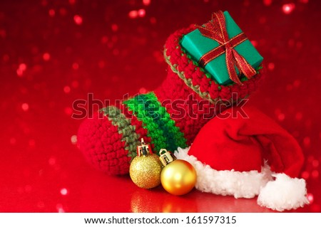 Small Christmas stocking and Santa hat on red sparkle background. Christmas stocking, Santa hat and ornament on red background.  - stock photo