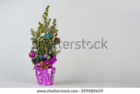 small christmas tree isolated on grey background - stock photo