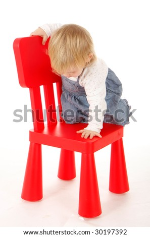 small climbing on red chair young girl - stock photo