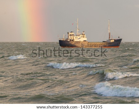 Small coastal vessel in the waters of the dutch Ijsselmeer, rainbow on the background