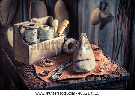 Small cobbler workplace with tools, leather and shoes - stock photo