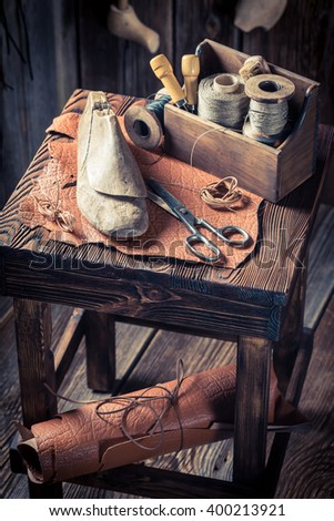 Small cobbler workshop with tools, shoes and laces - stock photo