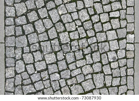 small cobblestone sidewalk made of cubic stones - tileable texture - stock photo