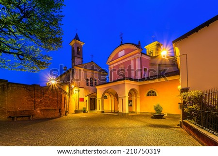 Small cobblestone square and two churches illuminated by lamppost early in the morning in town of Barolo, Italy. - stock photo