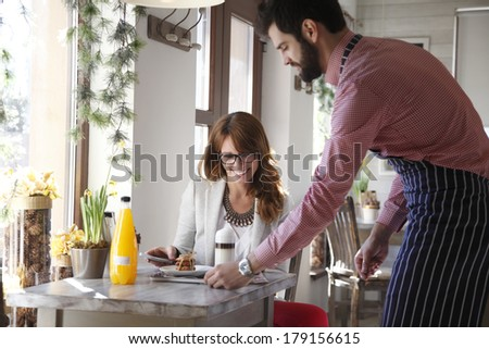 Small coffee shop owner serving coffee in his bistro.  - stock photo