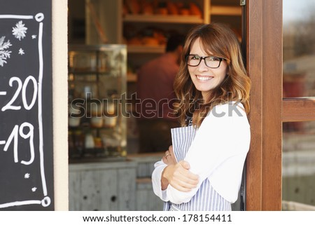 Small coffee shop owner standing in front of store. - stock photo