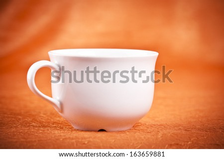 Small color coffee cup on orange fabric background - stock photo