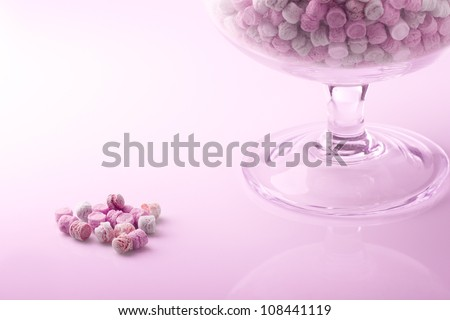 small colored candies in a glass jar and some out - stock photo
