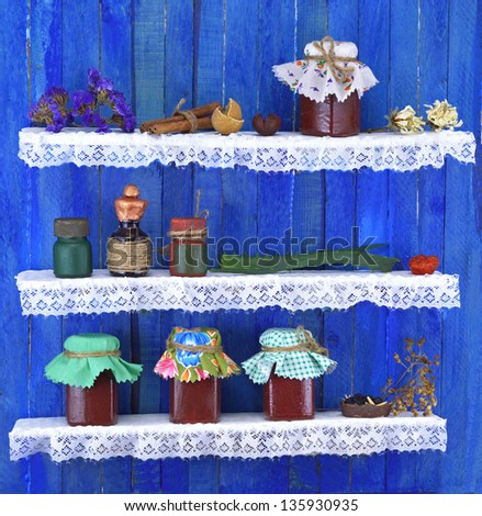 Small colorful bottles with healing remedies and dried herbs on shelves - stock photo