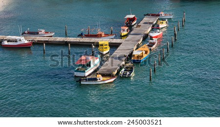 Small colorful fishing boats tied to a wood pier in Aruba - stock photo