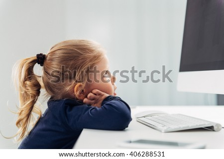 Small concentrated girl looking at monitor, studying pc. Concept of on-line education and application.  - stock photo