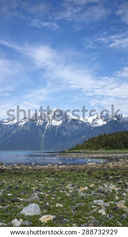Small cove off the Lynn Canal in Southeast Alaska in summer with mountains in the background. - stock photo
