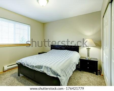 Small cozy bedroom with closet, beige carpet floor, black wood bed and nightstands - stock photo