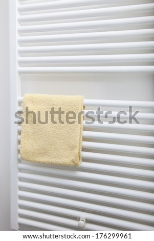Small cream coloured hand towel hanging on the wall mounted bars of a white bathroom radiator, closeup view