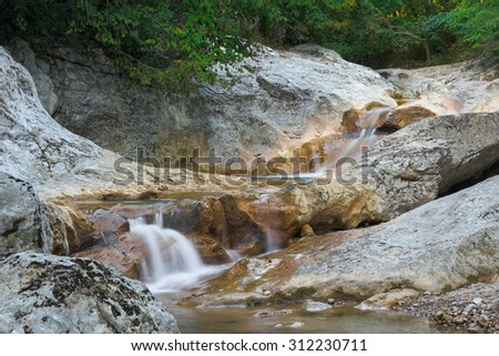 Small creek is flowing through complex rocky forms under green branches - stock photo