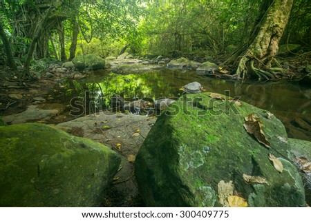 Small creek near waterfall with and rocks formation in the foreground. - stock photo