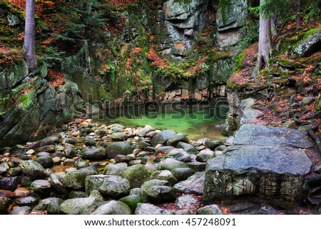 Small creek pool at rocky cliifside in the autumn mountains wilderness, Sudetes, Poland