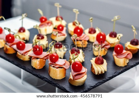 Small crostini with grilled baguette, cherry tomatoes, ham slices, cheese and fresh grapes on black background. Sandwiches or assorted canapes on a dark board, top view. - stock photo