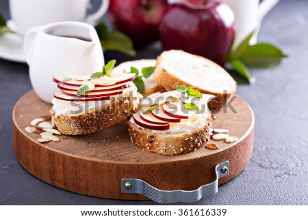 Small crostini with ricotta and apple on cutting board - stock photo
