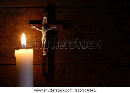 Small crucifix hanging on old wooden wall near lighting candle - stock photo