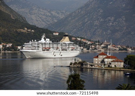 Small cruiser arriving in the inlet of Kotor - Montenegro. - stock photo