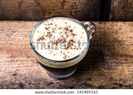 Small cup of espresso coffee in glass with foam and chocolate on old wooden table over vintage  background Closeup, - stock photo