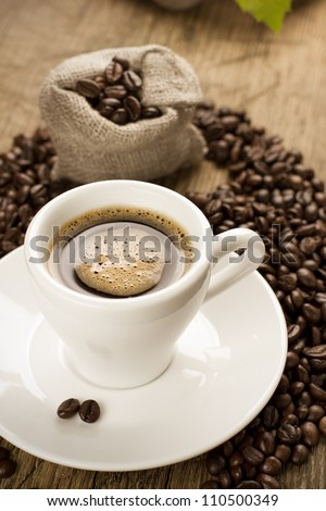 Small cup of strong coffee on a brown background with coffee beans - stock photo