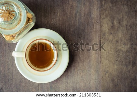 Small cup of tea with brown sugar on wood table background - stock photo