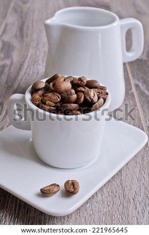 Small Cup of white filled the large coffee beans on a wooden surface - stock photo
