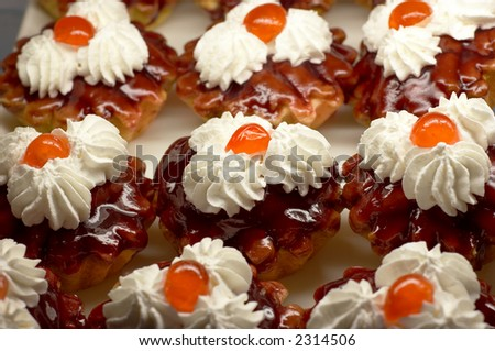 Small cupcakes with white cream and cherry on top. Shallow DOF. - stock photo
