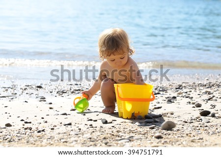 Small curious funny blonde child boy sitting on sea coast beach with wavy water sunny day outdoor playing with yellow plastic pail on natural background, horizontal picture