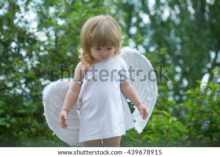 small cute baby boy with blonde long hair in white feathered angel wings and cloth outdoor on green natural background - stock photo