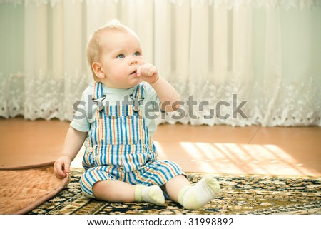 Small cute baby with finger in mouth - stock photo