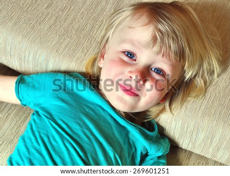 Small cute boy lying on the bed  - stock photo