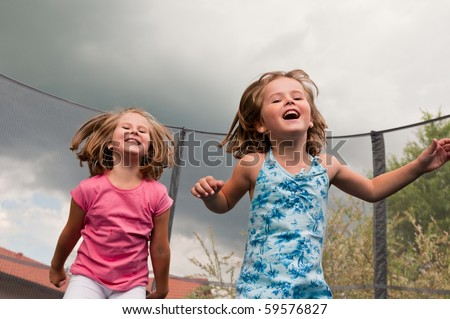 Small cute children jumping on trampoline - garden and family house in background - stock photo
