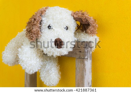 Small cute dog doll on yellow background. /toy