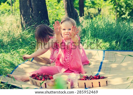 Small cute funny girls (sisters) at the picnic. Selective focus. - stock photo