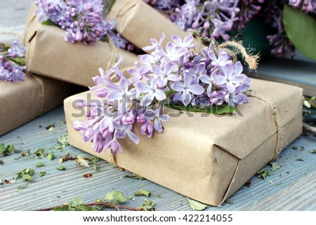 Small cute gift boxes wrapped with simple brown craft paper and decorated with natural lilac on old wooden background. Floral decor elements. Rustic design - stock photo