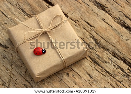 Small cute gift boxes wrapped with simple grey craft paper and jute decorated with red wooden ladybird. Handmade decor elements, rustic design