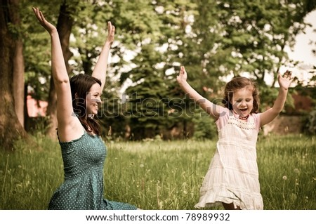 Small cute girl enjoying life with her mother outdoors in park - stock photo