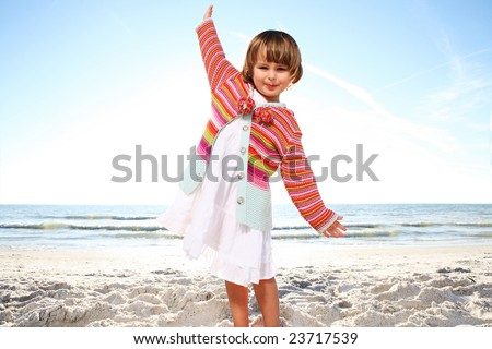 Small cute girl enjoying sunny day at the beach. Shoot against the sun. - stock photo