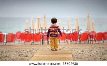 Small cute girl on the beach - stock photo