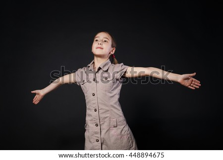Small cute girl openes hands in fly gesture at black background. Portrait of little female child dreaming - stock photo