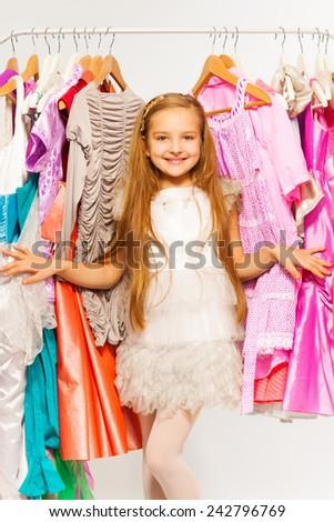 Small cute girl standing between hangers in shop - stock photo